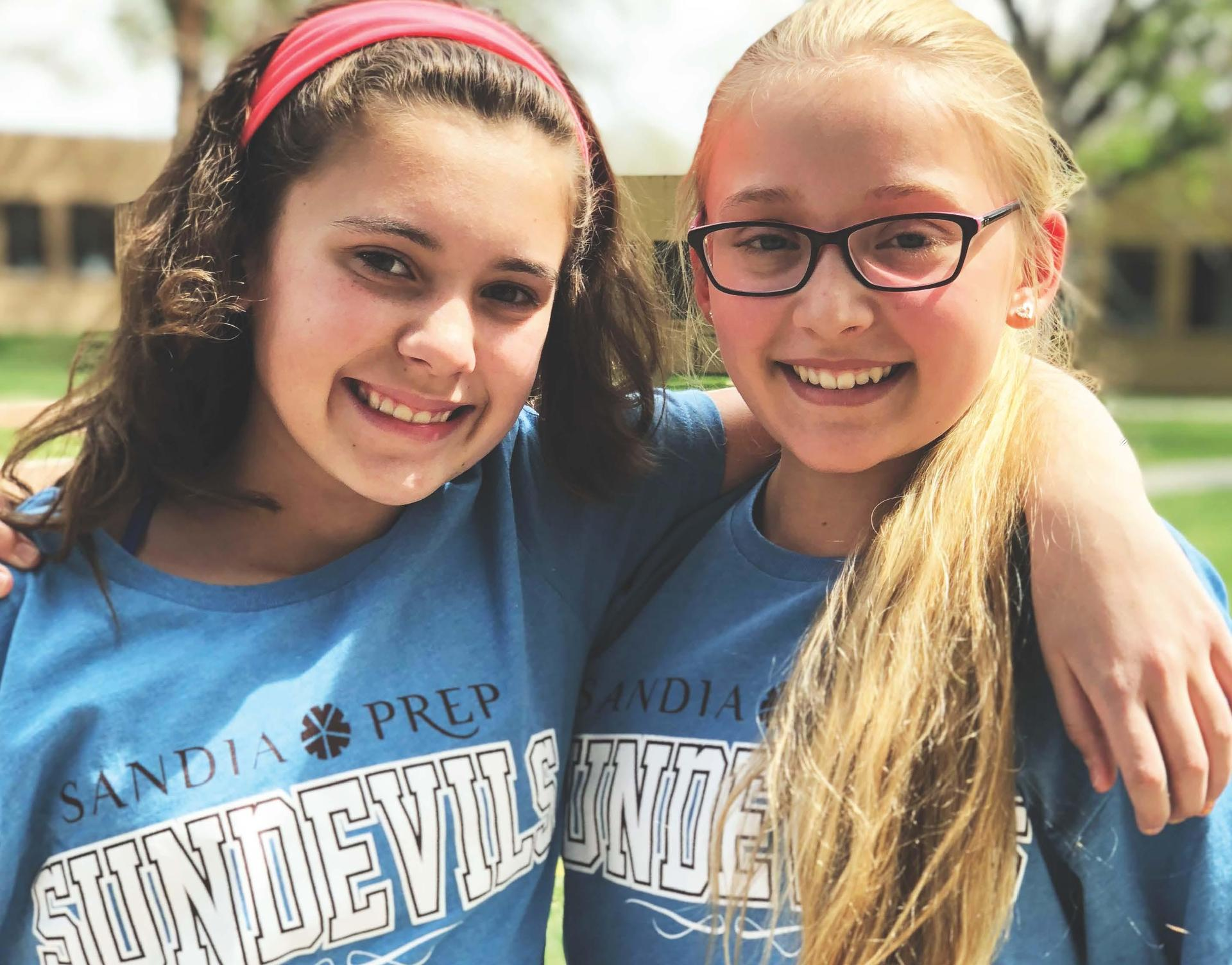 Two middle school girls wearing Sandia Prep shirts smile and look at camera