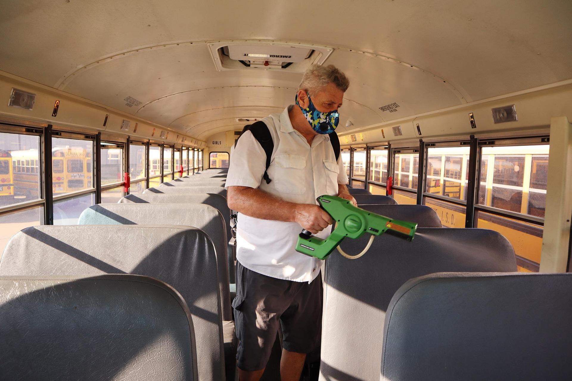 man sanitizing school bus seats