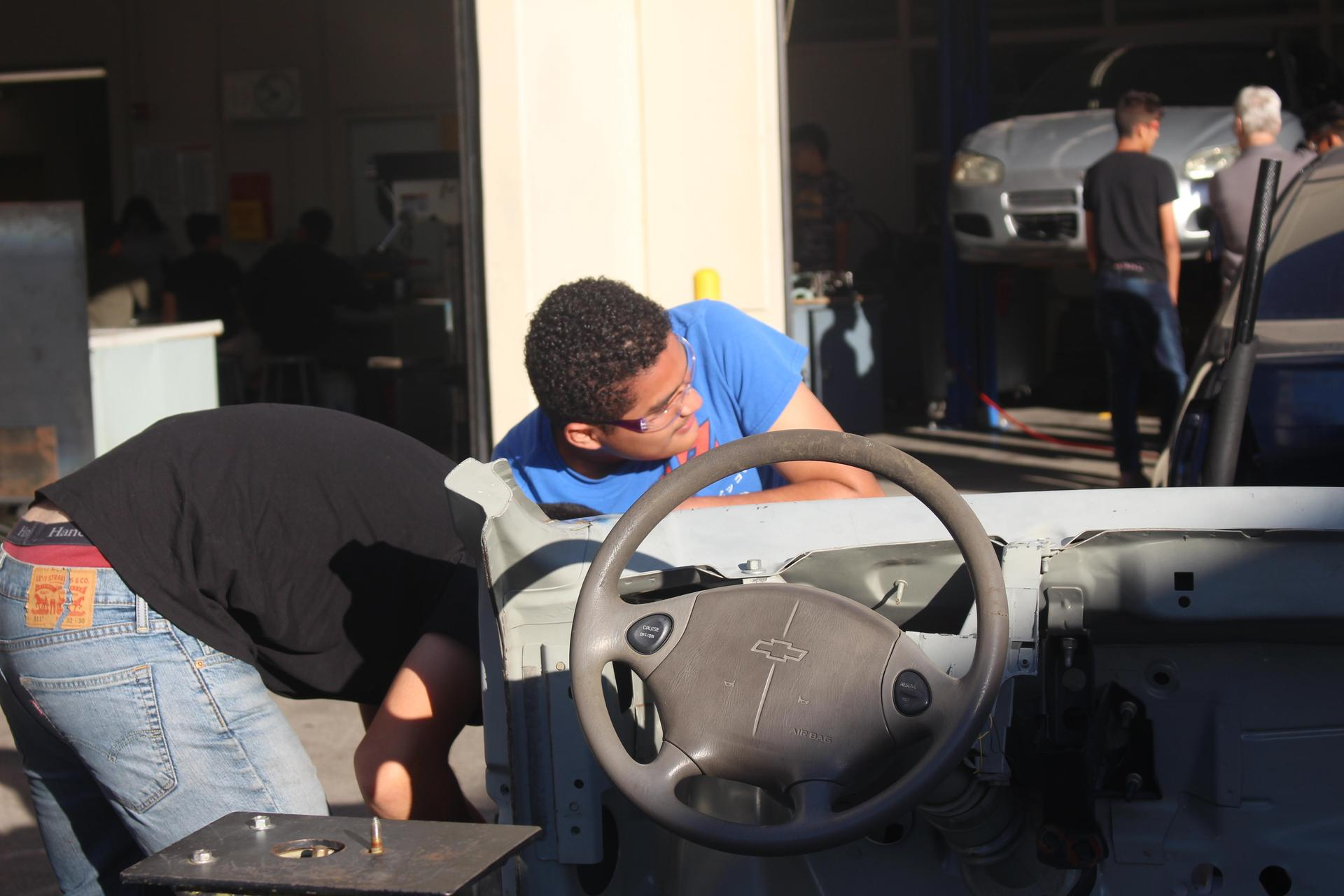 Students working on a car body