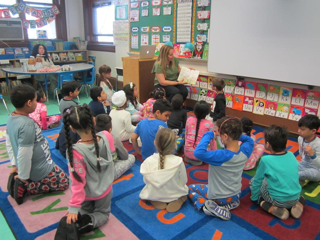 children wearing pj's while parent reads to them
