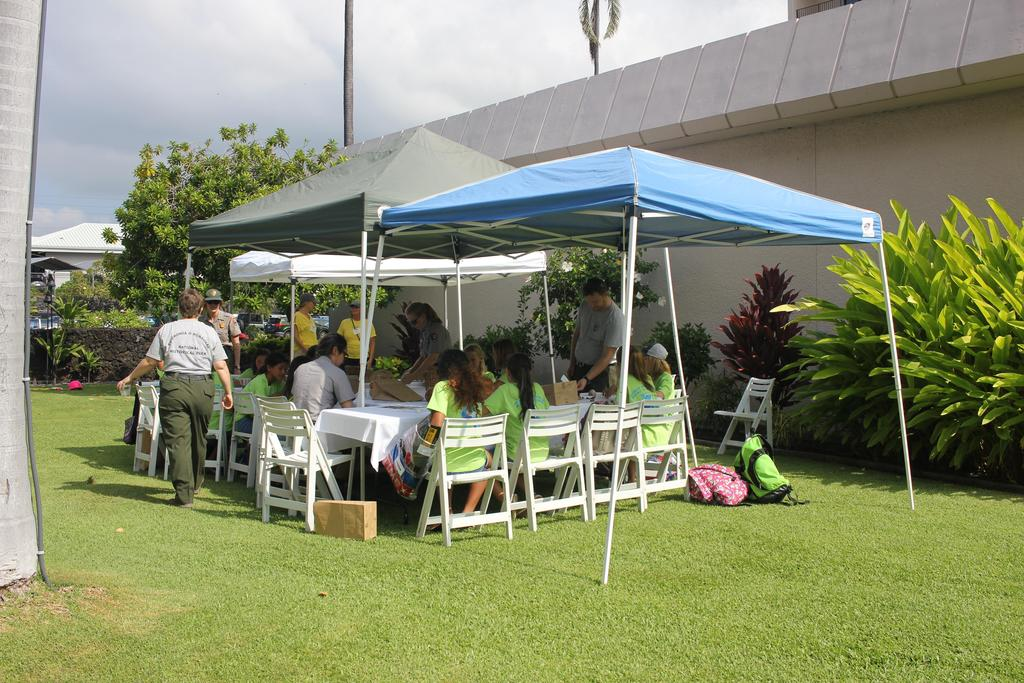 listening to presentation outside under a canopy