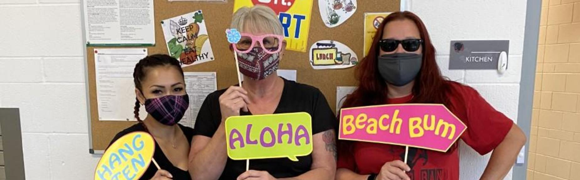 Three ladies posing with Hawaiian theme props.