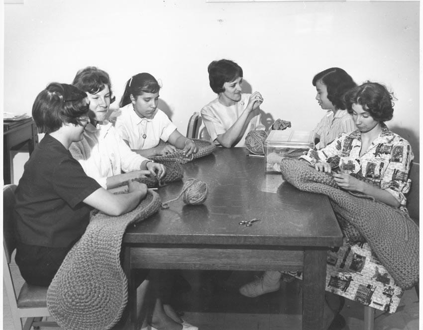 Teacher with 5 girls that are knitting and making a weave rug.
