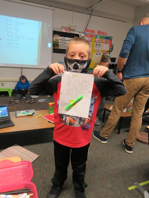 A student proudly displays the letter he wrote to his pen pal.