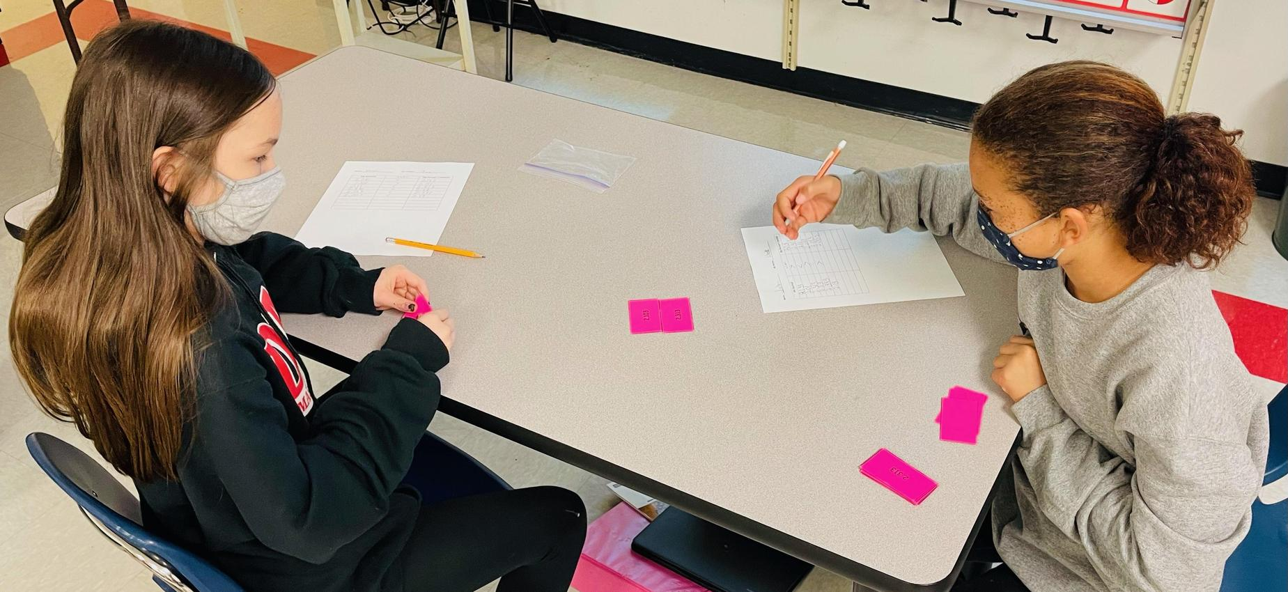 Two students work on math at a table.