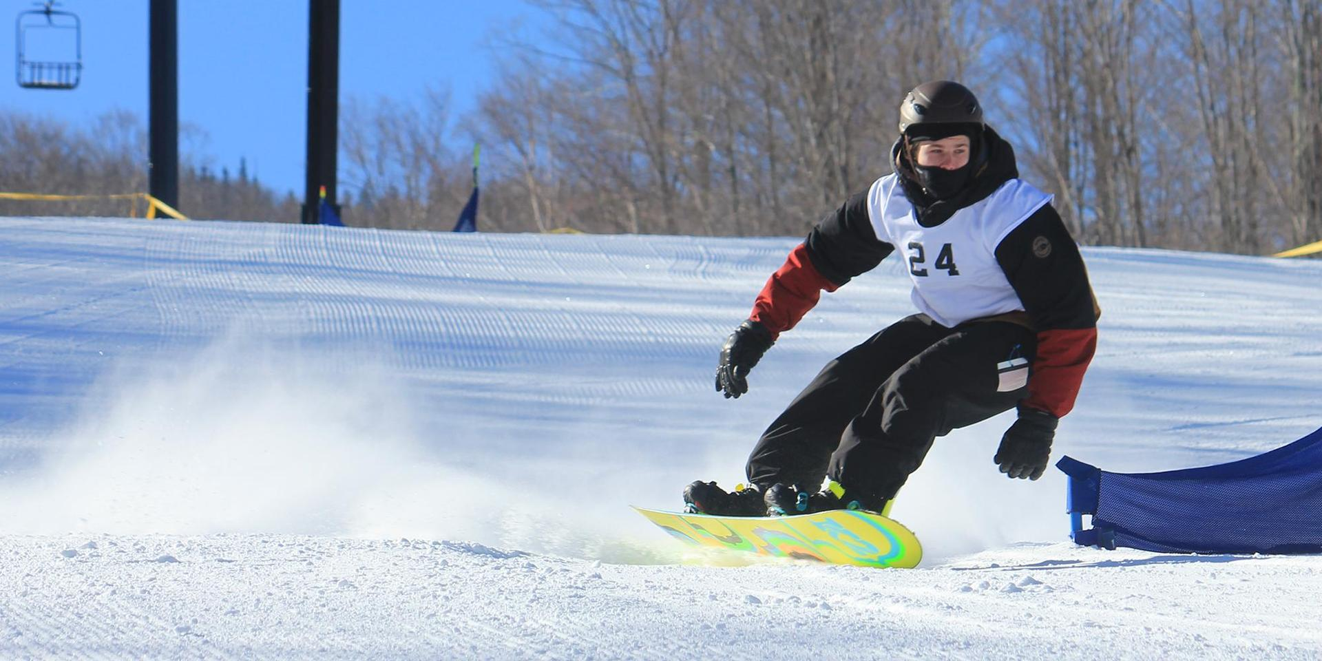 A student snowboarding down Cannon Mountain in a competition.