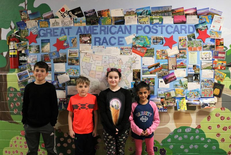 Photo of four Franklin Elementary 3rd graders in front of Great American Postcard Race bulletin board.