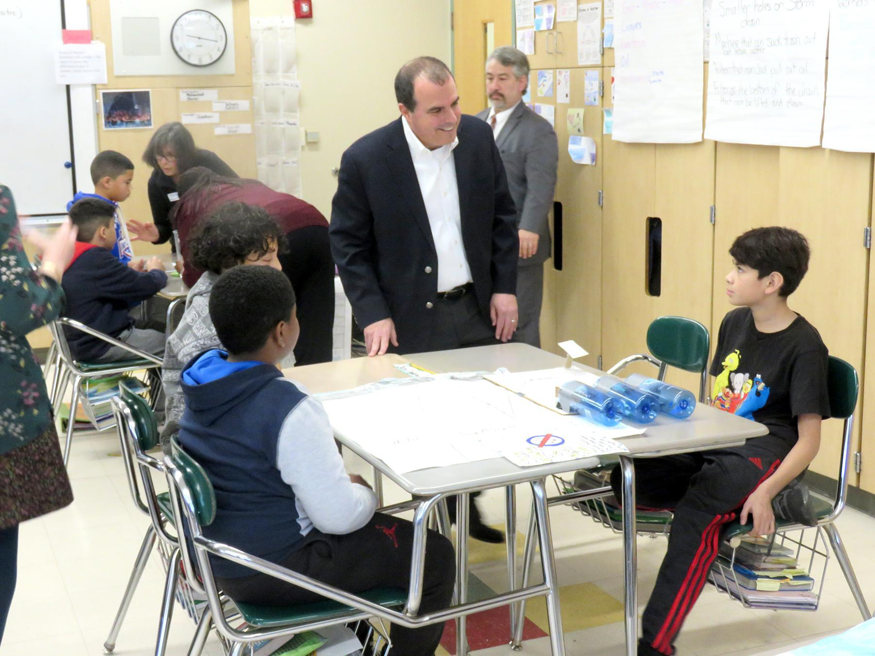Three students explain their project to a classroom visitor