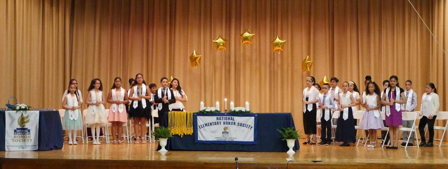2018 PS8 National Elementary Honor Society inductees stand on the school auditorium stage during the 2018-2019 National Elementary Honor Society induction ceremony.