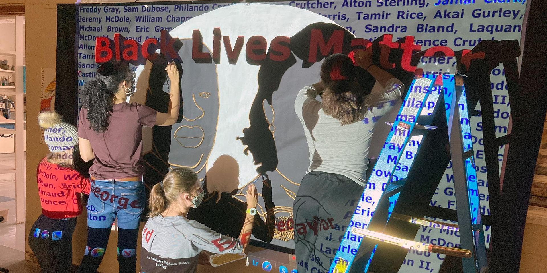 Student painting a Black Lives Matter mural.