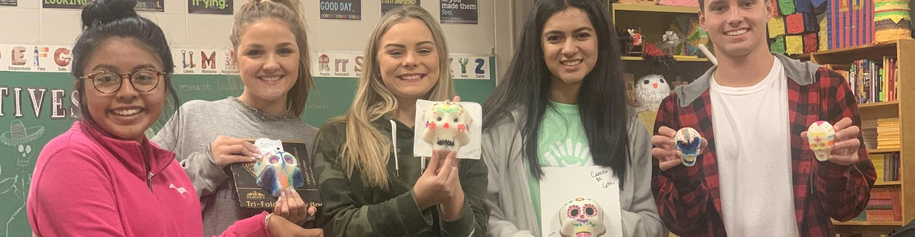 Students from Mayfield High School show off their sugar skulls, created in Mrs. Godinez's class for Dia de los Muertos!