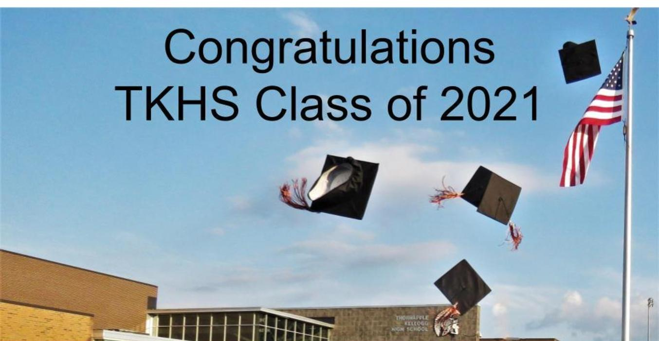 Congratulations Class of 2021 with hats flying in the air by American flag.