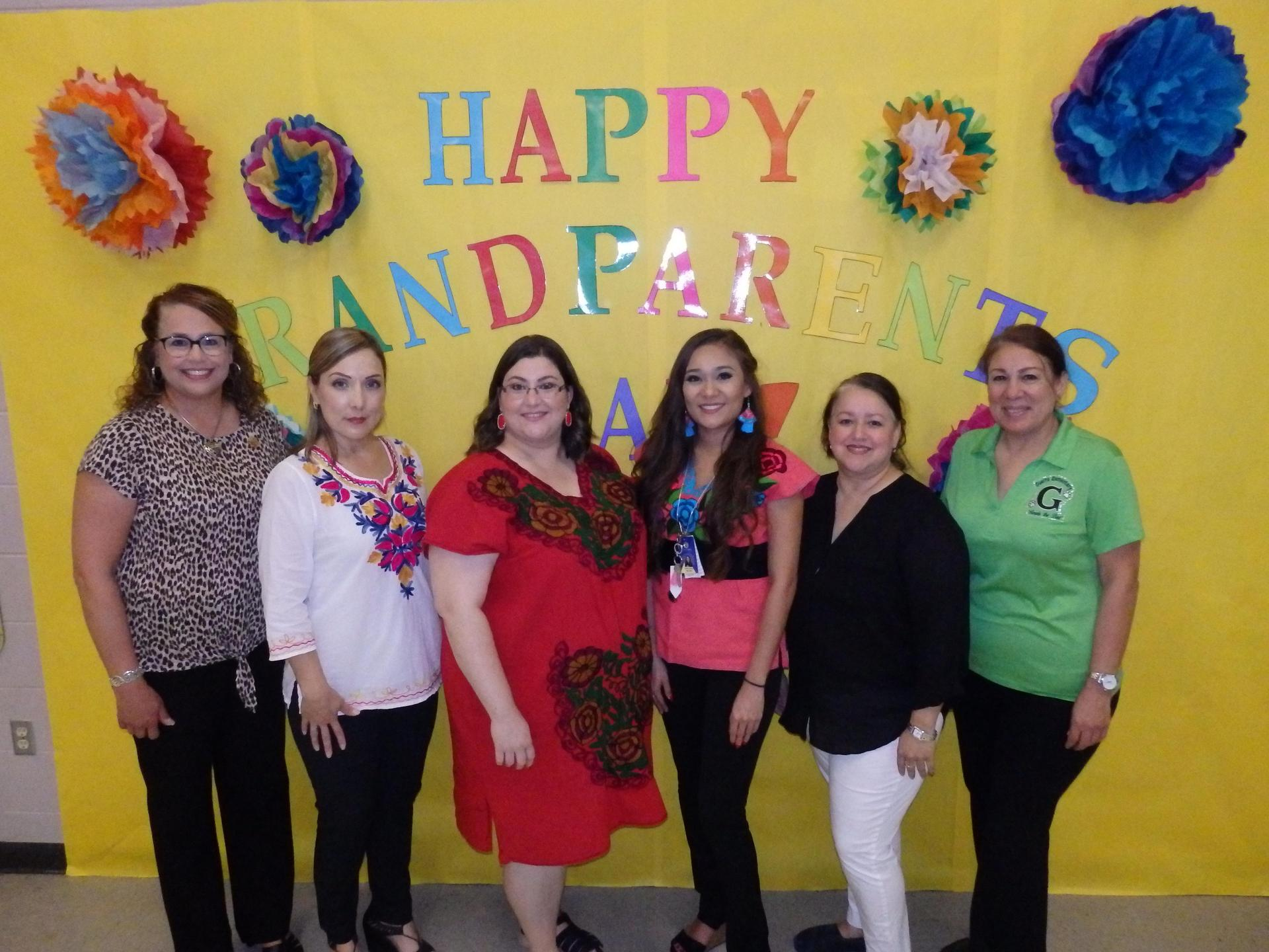 Principal and kinder teachers and paraprofessionals pose for picture