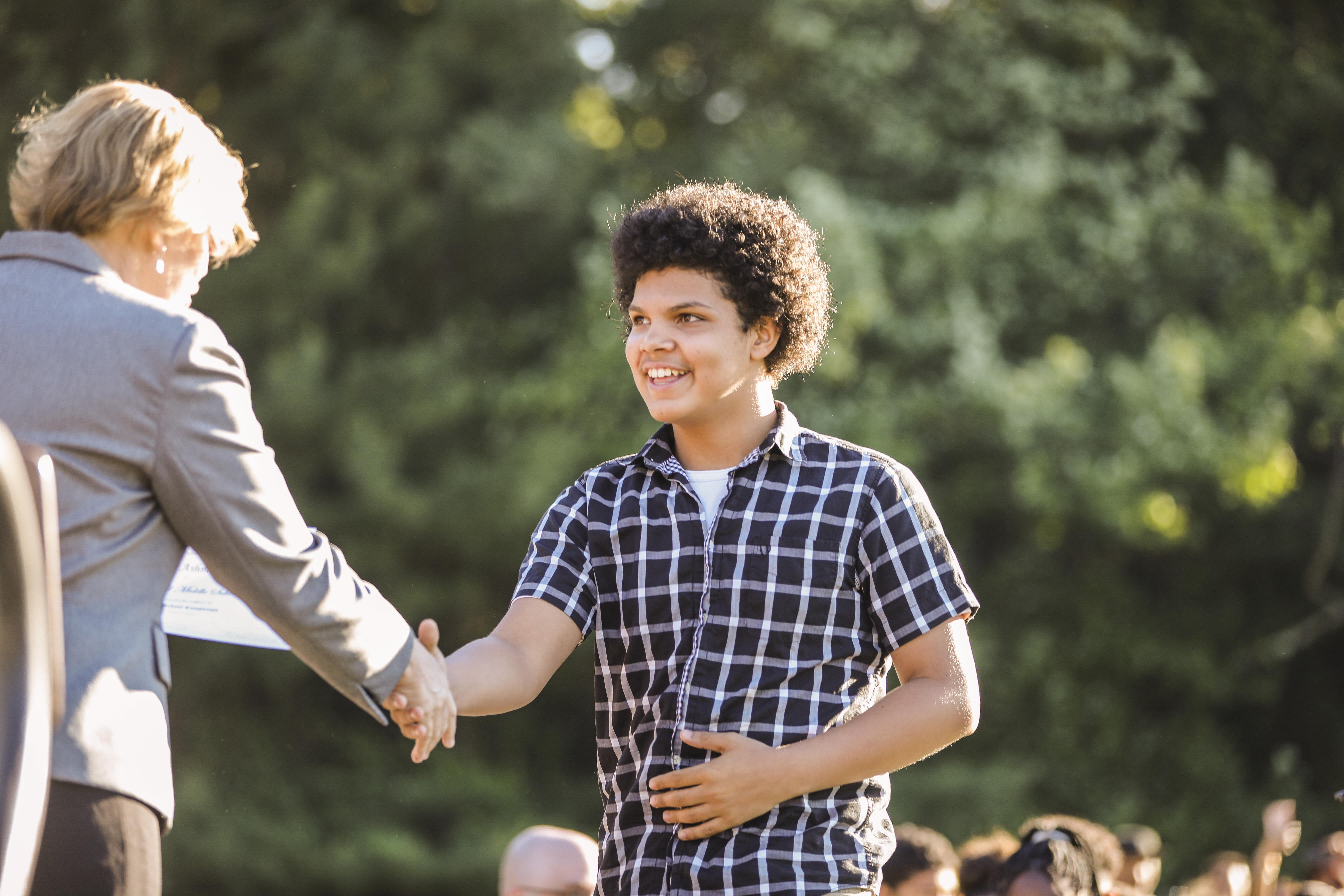 CHMS student shaking superintendent's hand at stepping forth ceremony