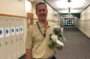 Principal holding Gus the dragon (stuffed animal)