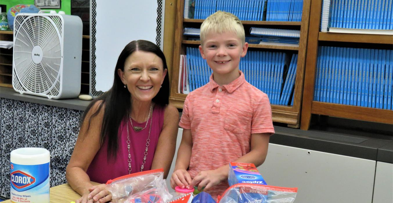 A young student meets his teacher during open house.