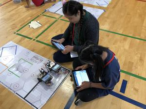 Students commanding robots to move with I Pads.