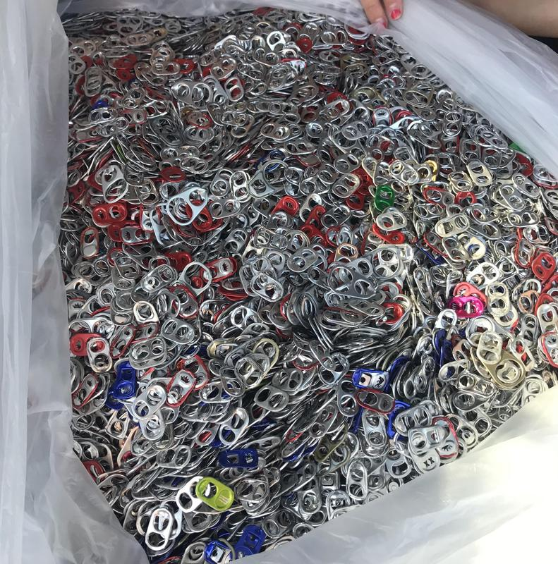 Thousands of pop tabs in a container