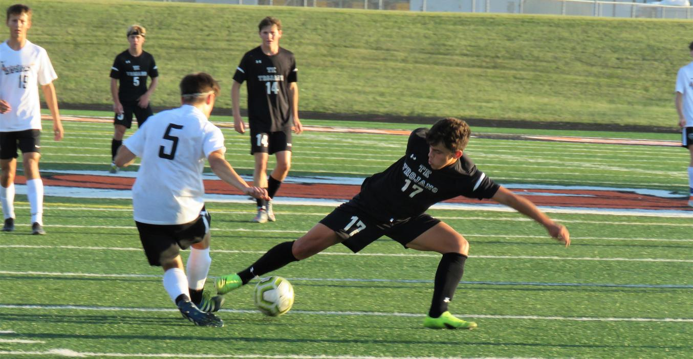 A TKHS varsity soccer player reaches for the ball.