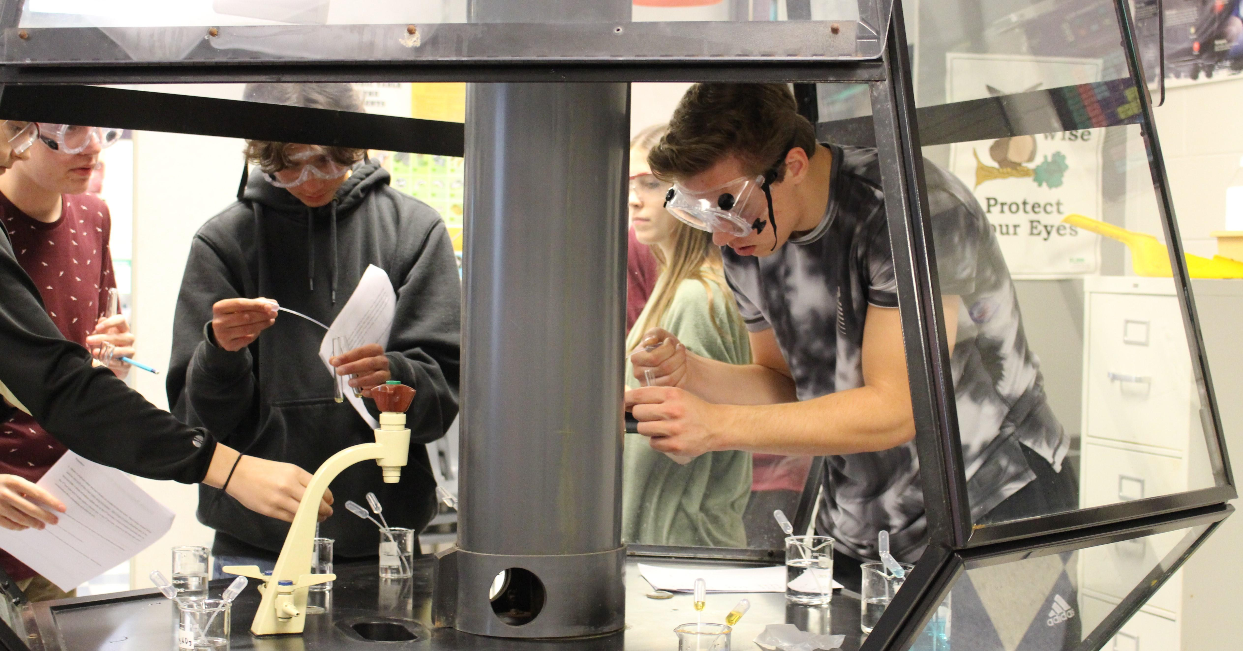 students wear goggles in chemistry while combining solutions in glass protective area