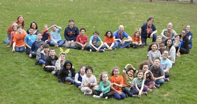 Elementary Students for a heart on the school lawn