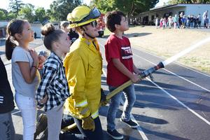 CAL FIRE Officer Jarrod Garrison with students from Yokayo Elementary at Career Day.