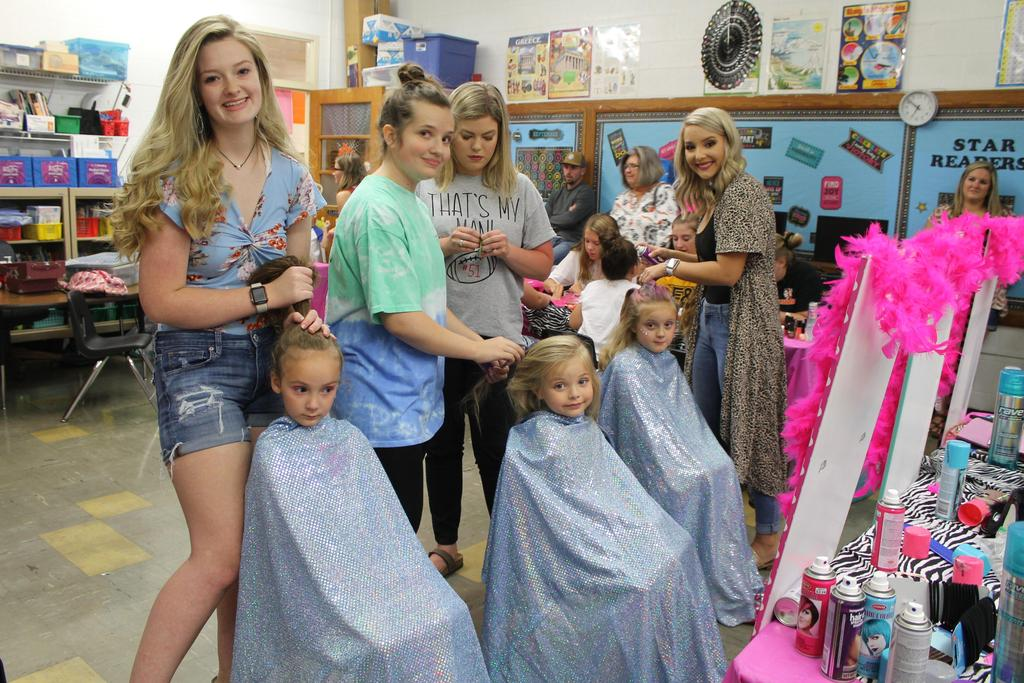 Students getting their hair done by CHS Cheerleaders at Fall Festival Princess Makeovers