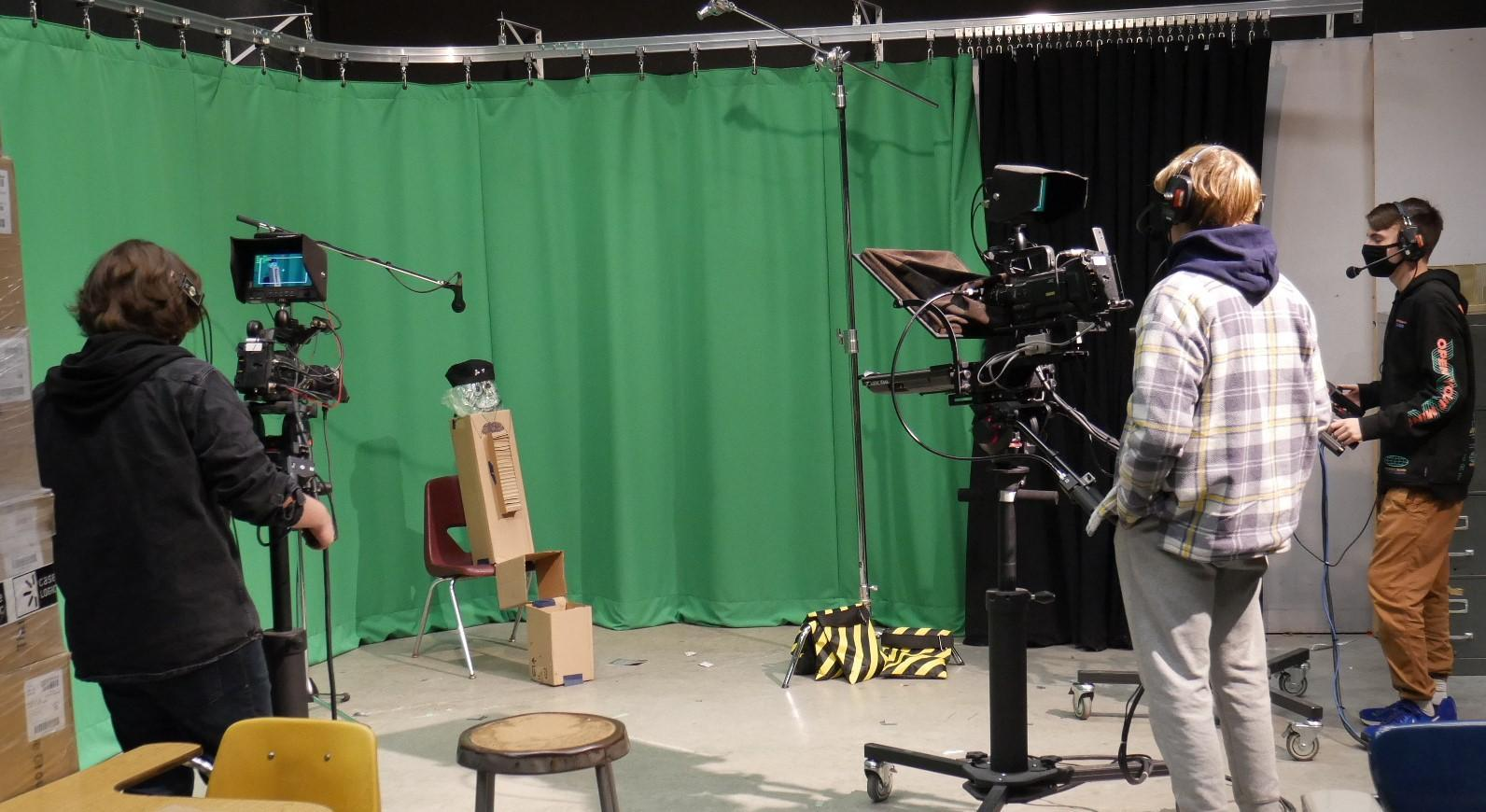 masked students working in front of green screen