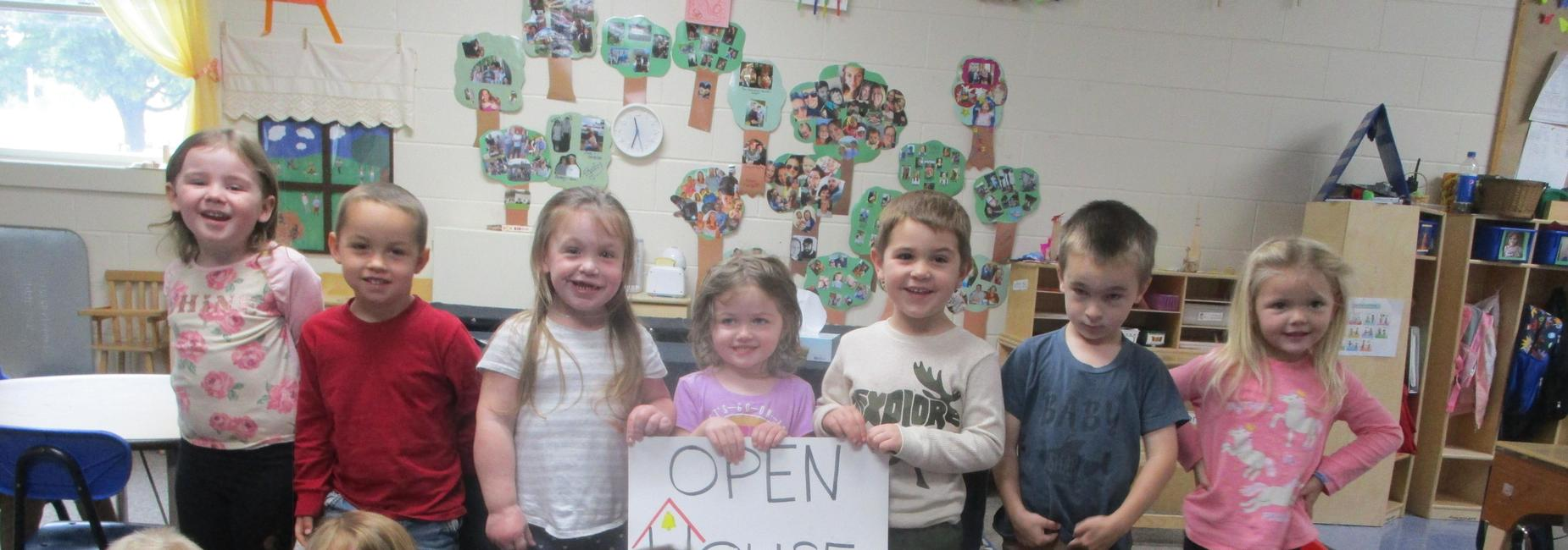 a group of children holding a sign that says Open House