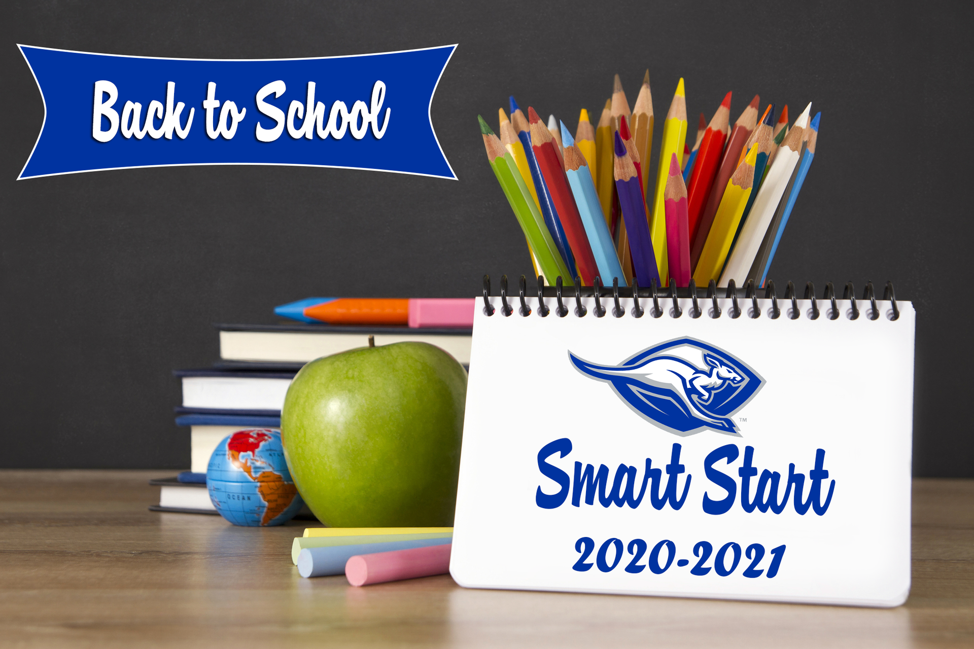 Back to school image with books, an apple, colored pencils, chalk, and a spiral index card with back to school wording.