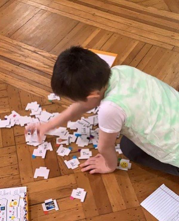 boy sitting on the floor trying to put his puzzle pieces together