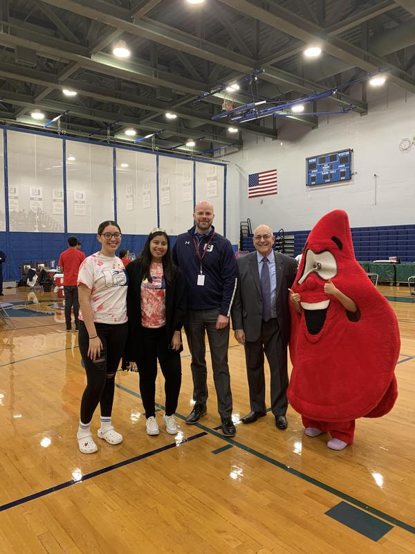 three HOSA students with principal lewis, board secretary Anthony Dragona and the blood drop mascot