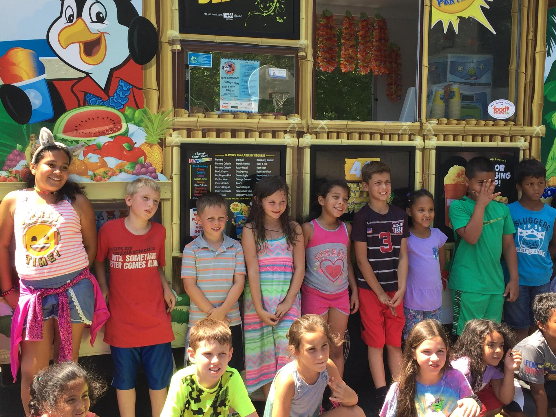 Group of children standing by Kona Ice Truck