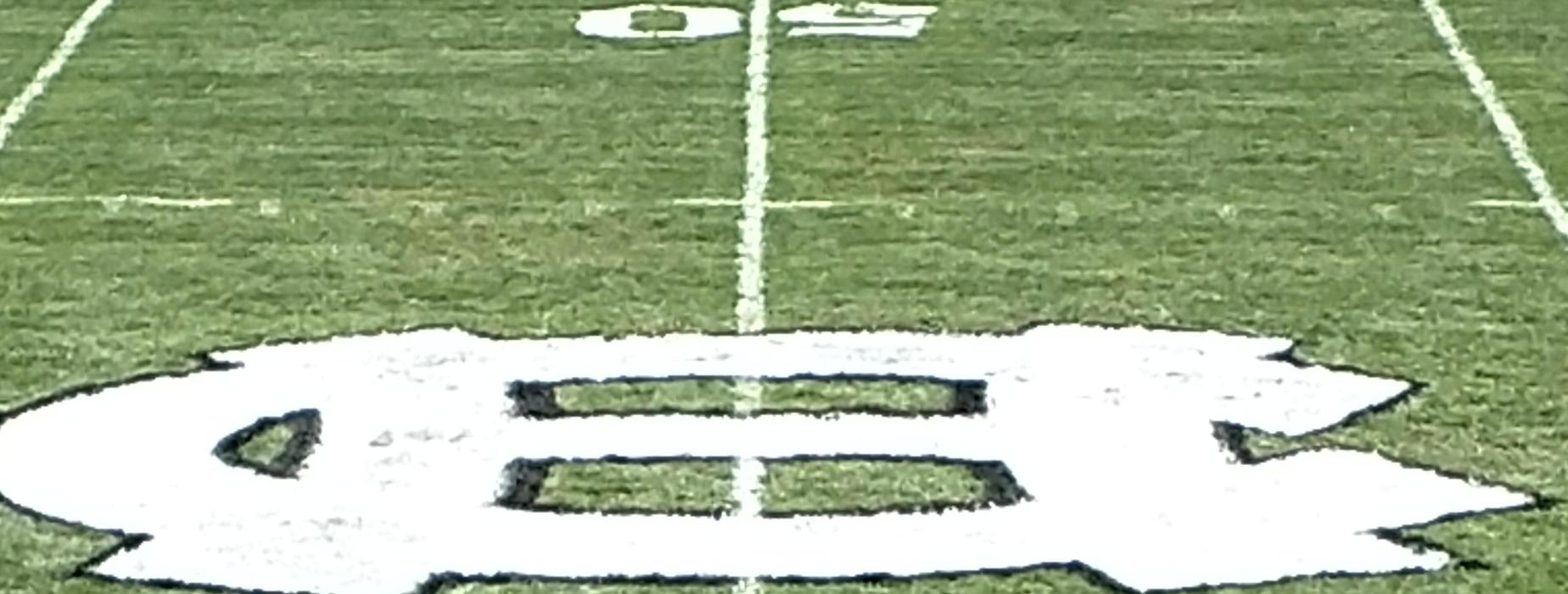 Homer-Center Logo on the 50 yard line on the football field.