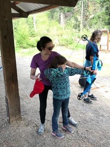 teacher showing a student how to use a bow and arrow