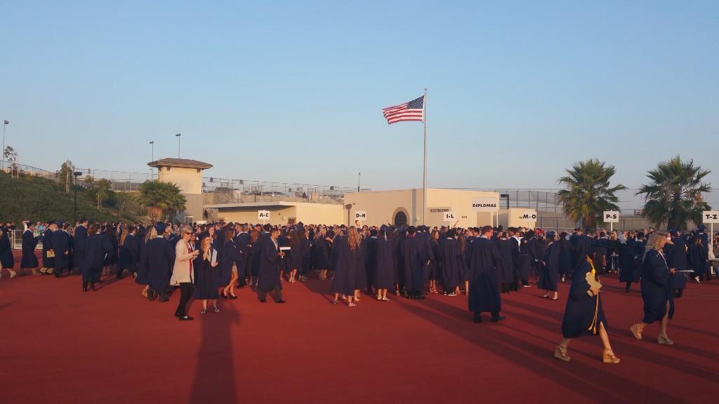 Students at graduation picking up their diplomas