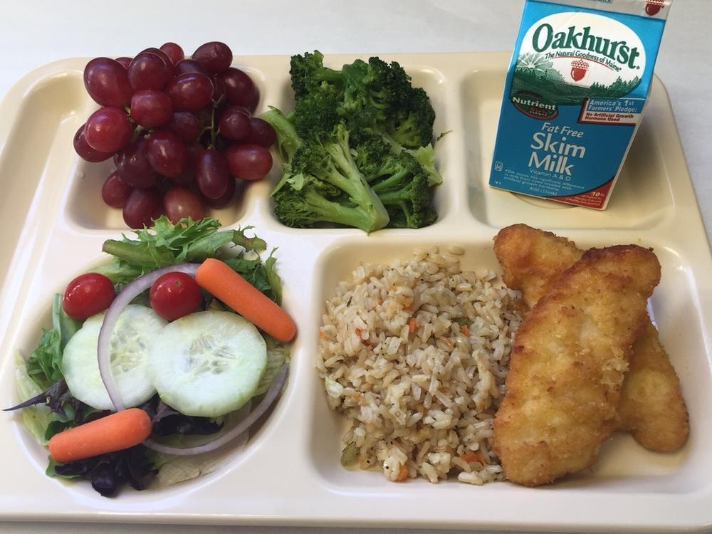 Chicken Tenders, Rice Pilaf, Salad, Broccoli, Grapes and Milk