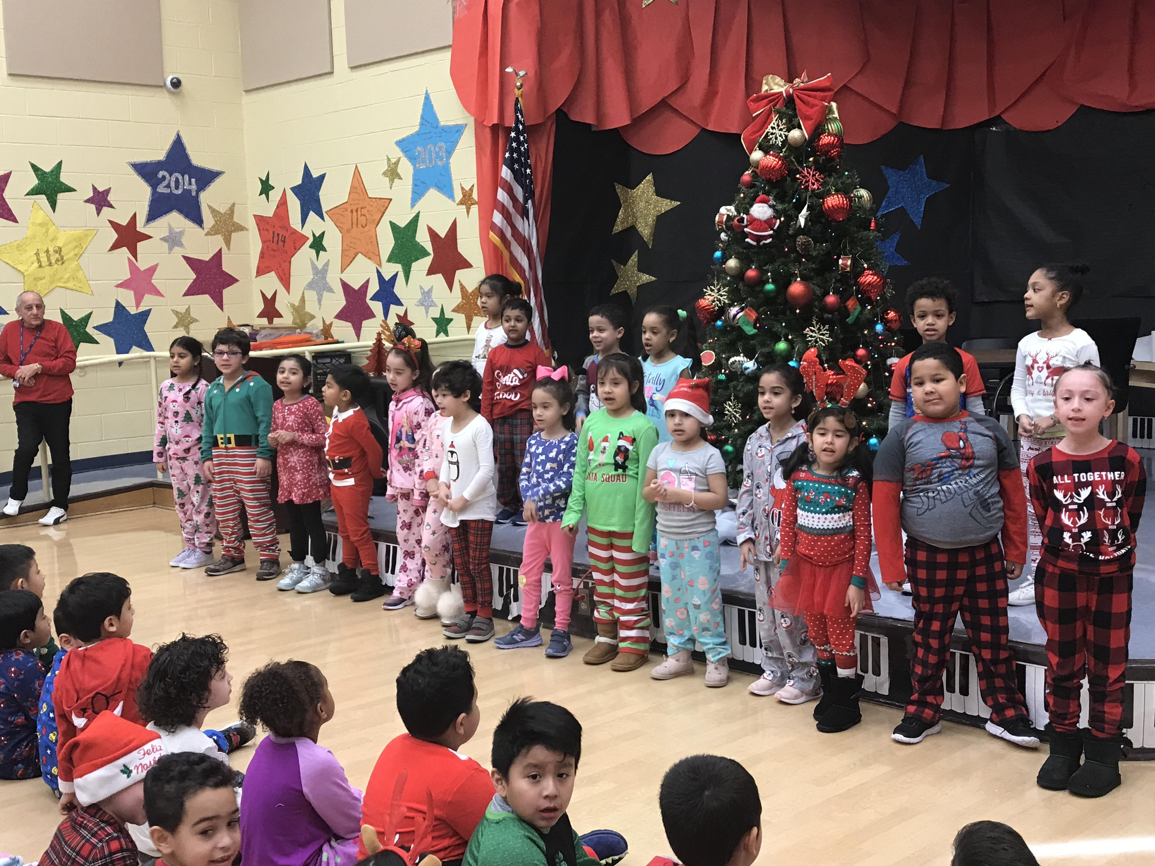 children in their pj's on stage in front of the Christmas Tree Signing