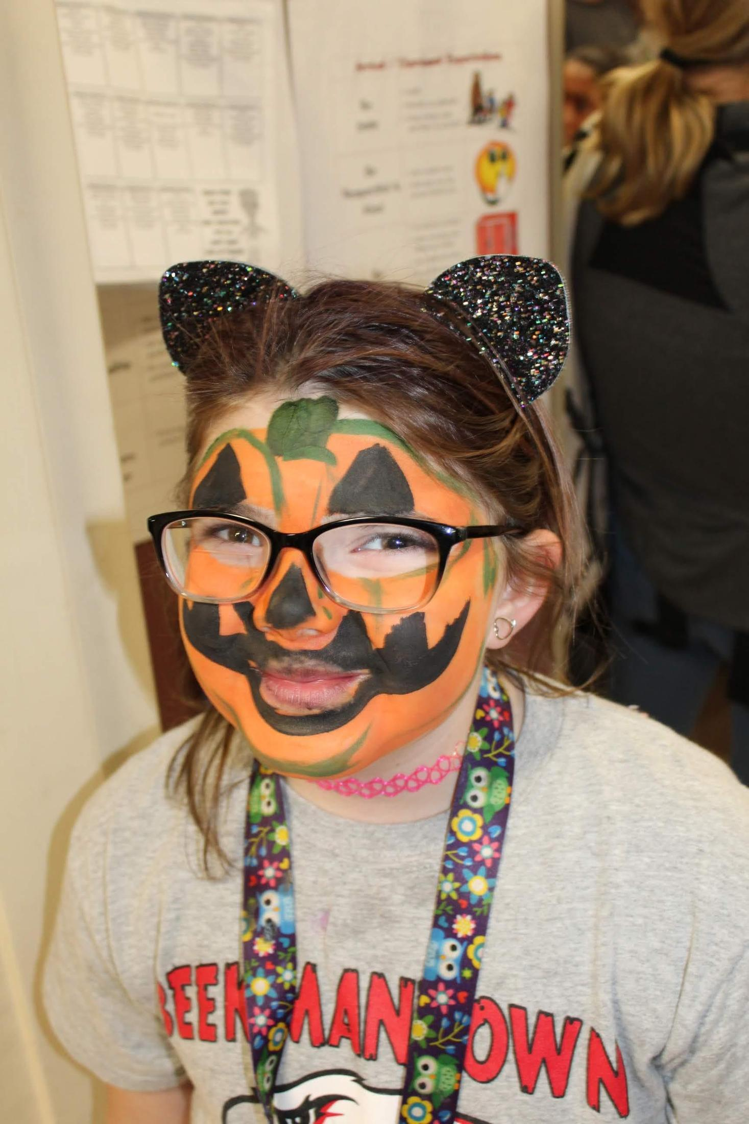 Student showing off her pumpkin face paint.