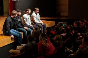 Four players sit on the stage to talk to kids in the auditorium.
