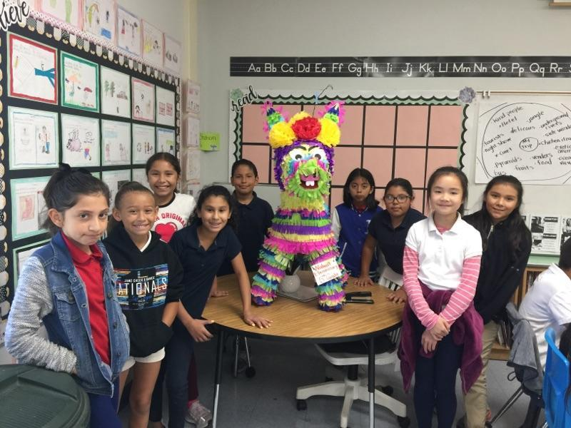 Students stand next to their class piñata