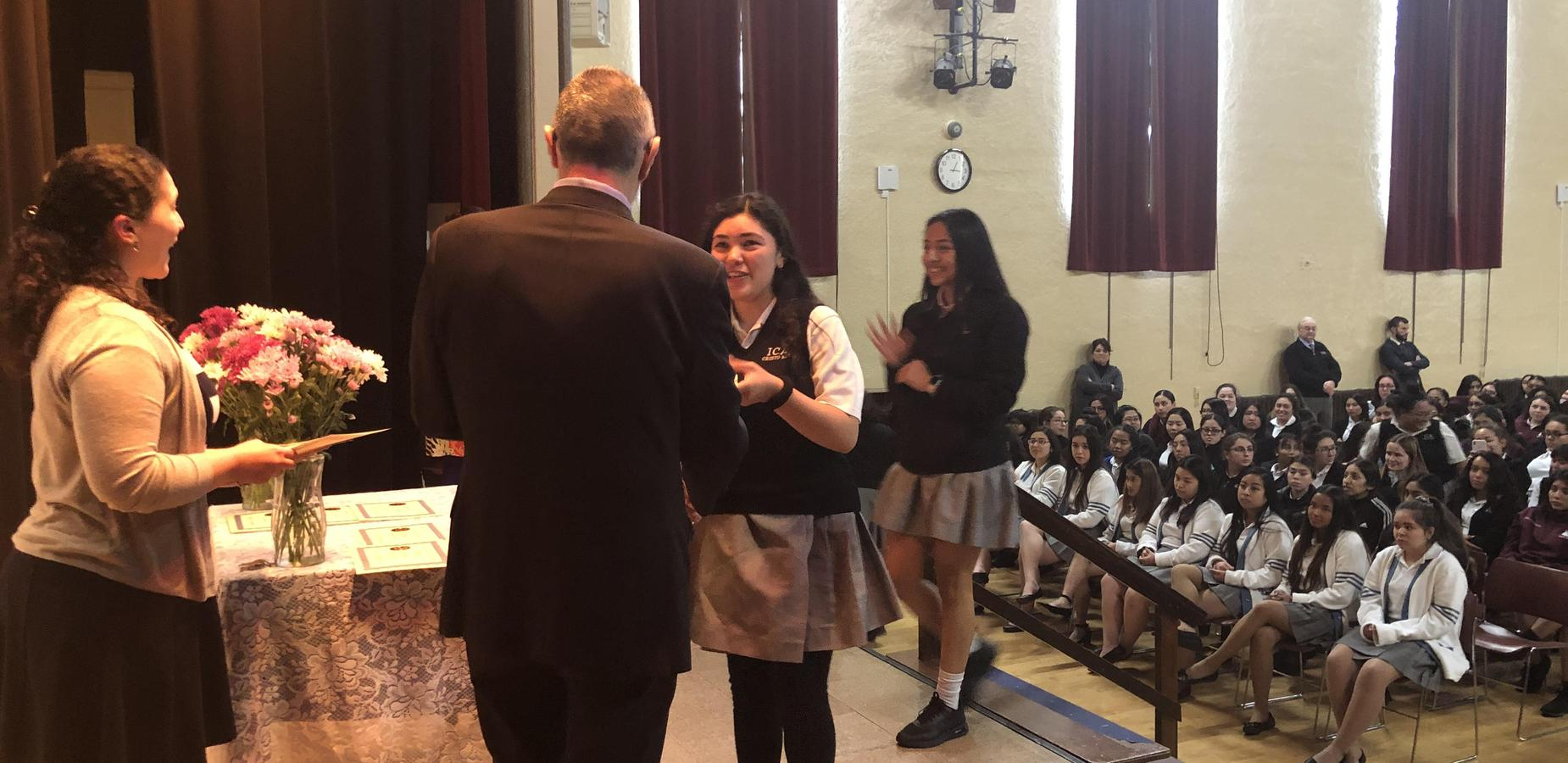 principal handing student honors award on stage at assembly