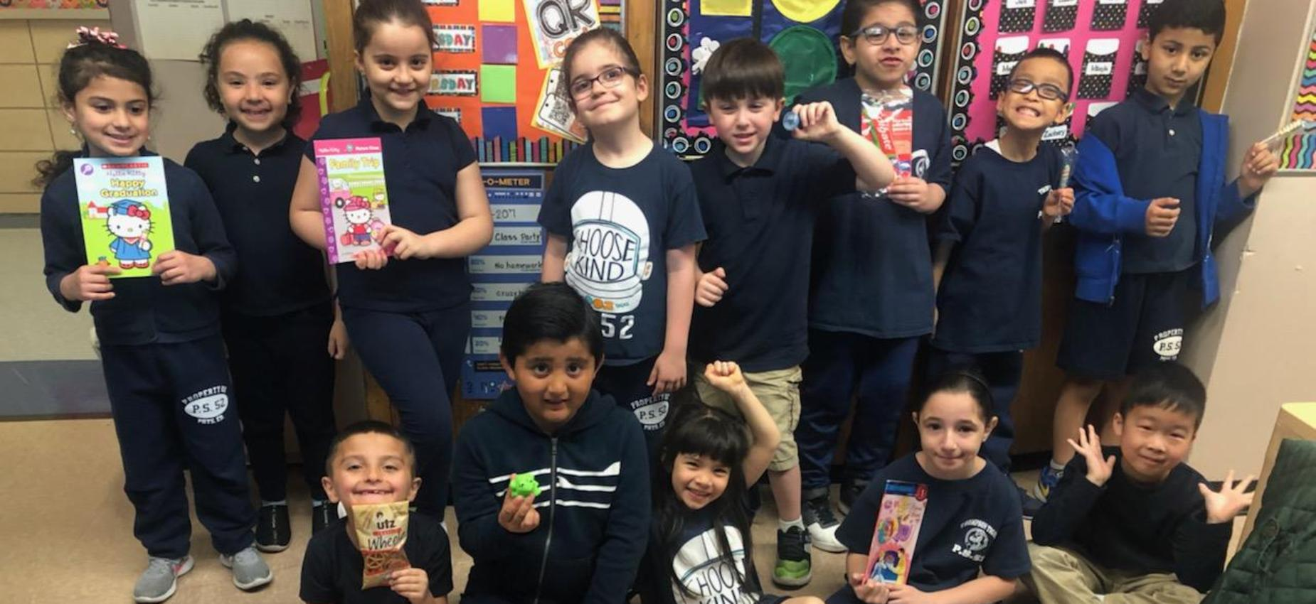 second graders holding up books