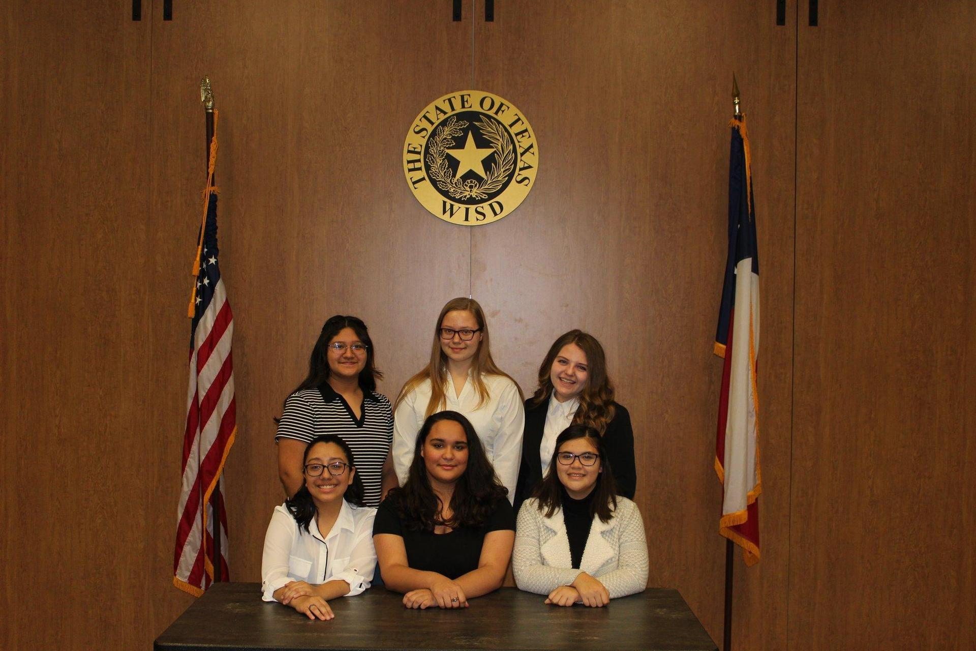 group of criminal justice students pose with texas & american flags