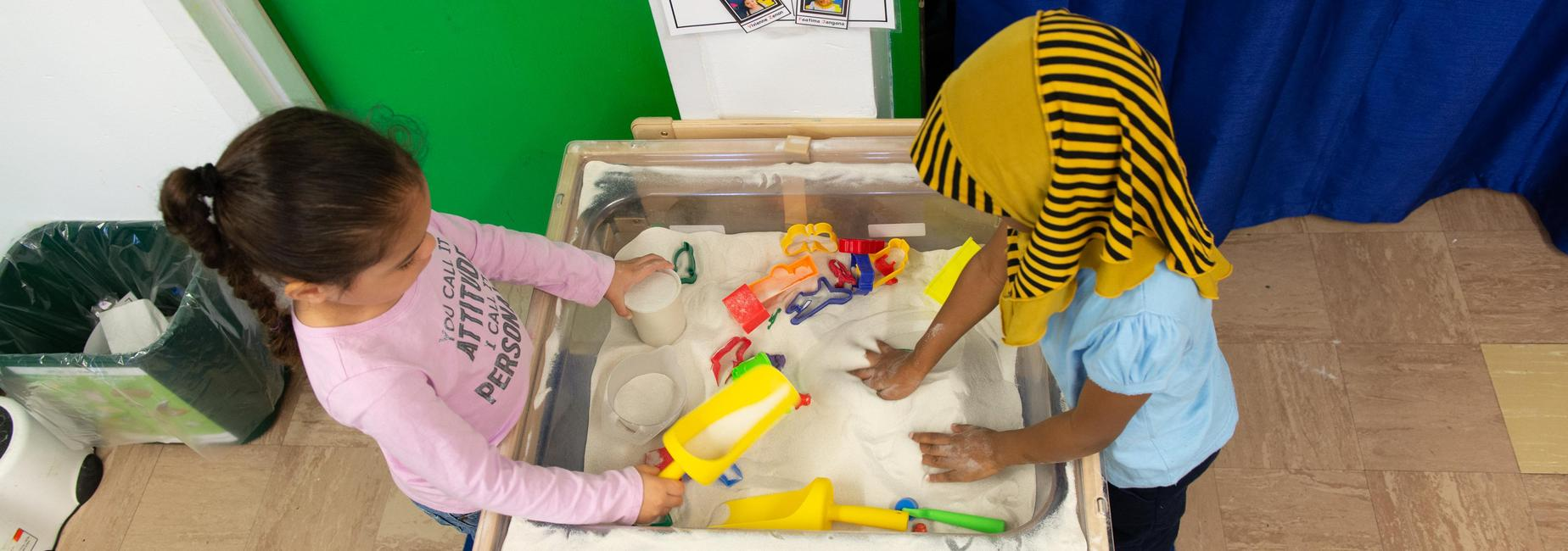 Two pre-k students playing at a sand table.