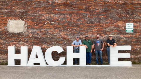 4 men standing against a brick wall as the I in the word hachie