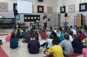 musician singing and playing guitar in front of students.