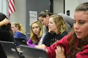 Students using Chromebooks in the classroom with teacher looking on and assisting