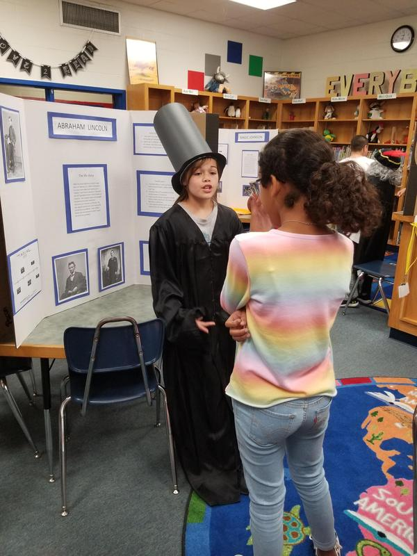 girl dressed as Abraham Lincoln talking to student