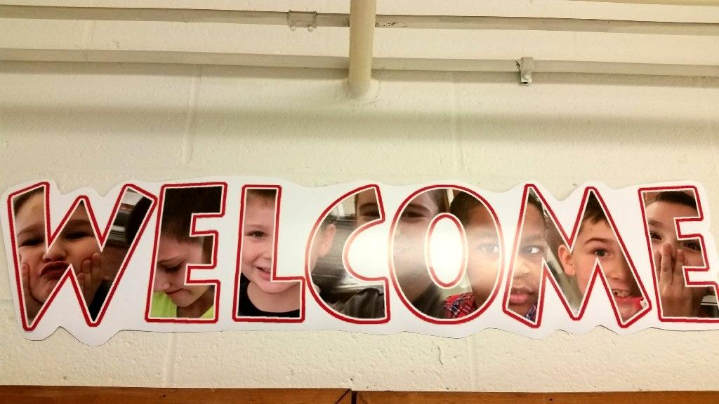 Welcome sign with student faces